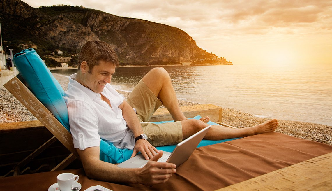 Man Looks At His Laptop While Sitting On The Beach At Sunset, Travel Trends