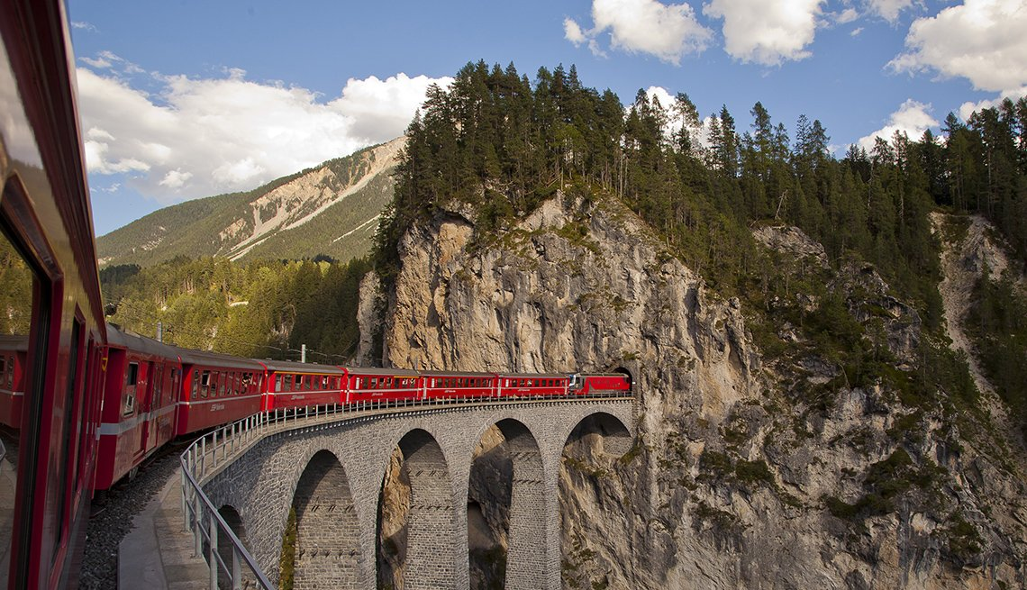 Red Train Crosses Over The Bridge With Scenic Mountains In Background On The Bernina Express In Switzerland, Scenic Railways