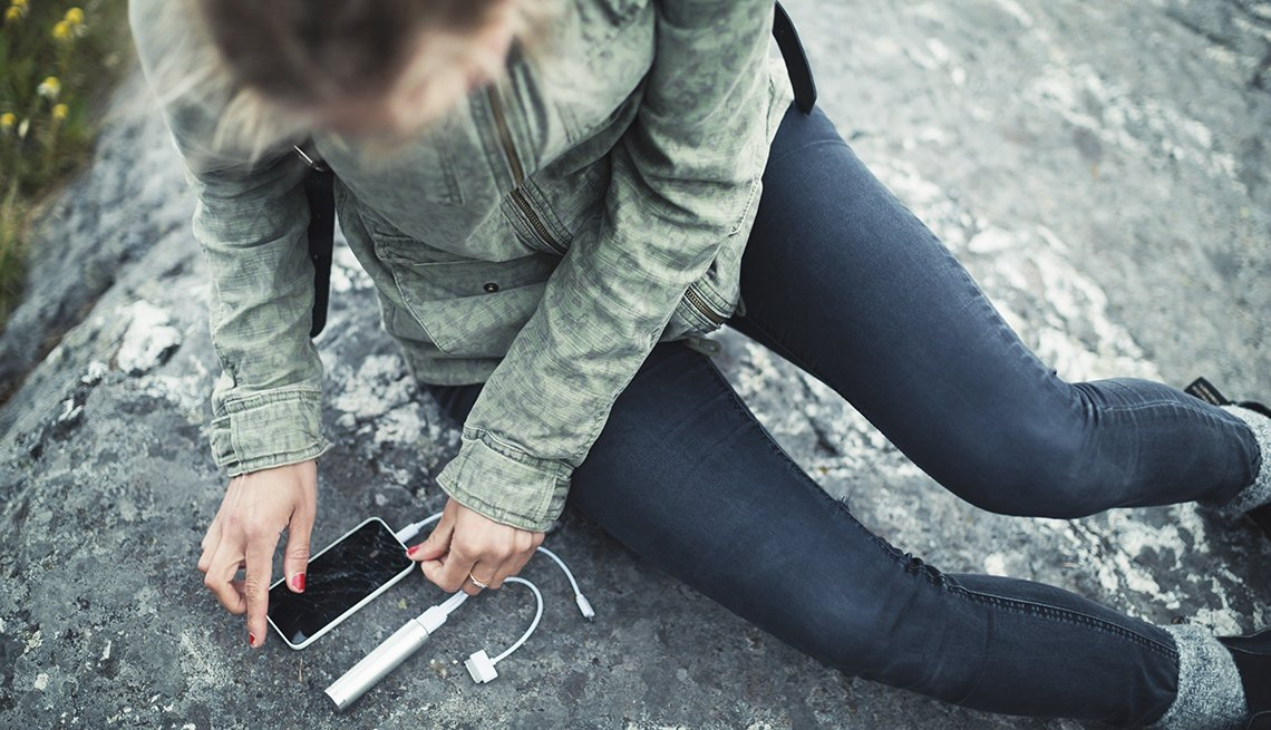 Young Caucasian Woman Looks At Her Phone With A Charger Attached While Hiking, Gifts For Travelers