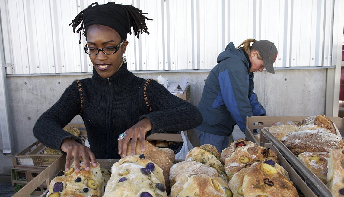 woman inspects bread at farmers market