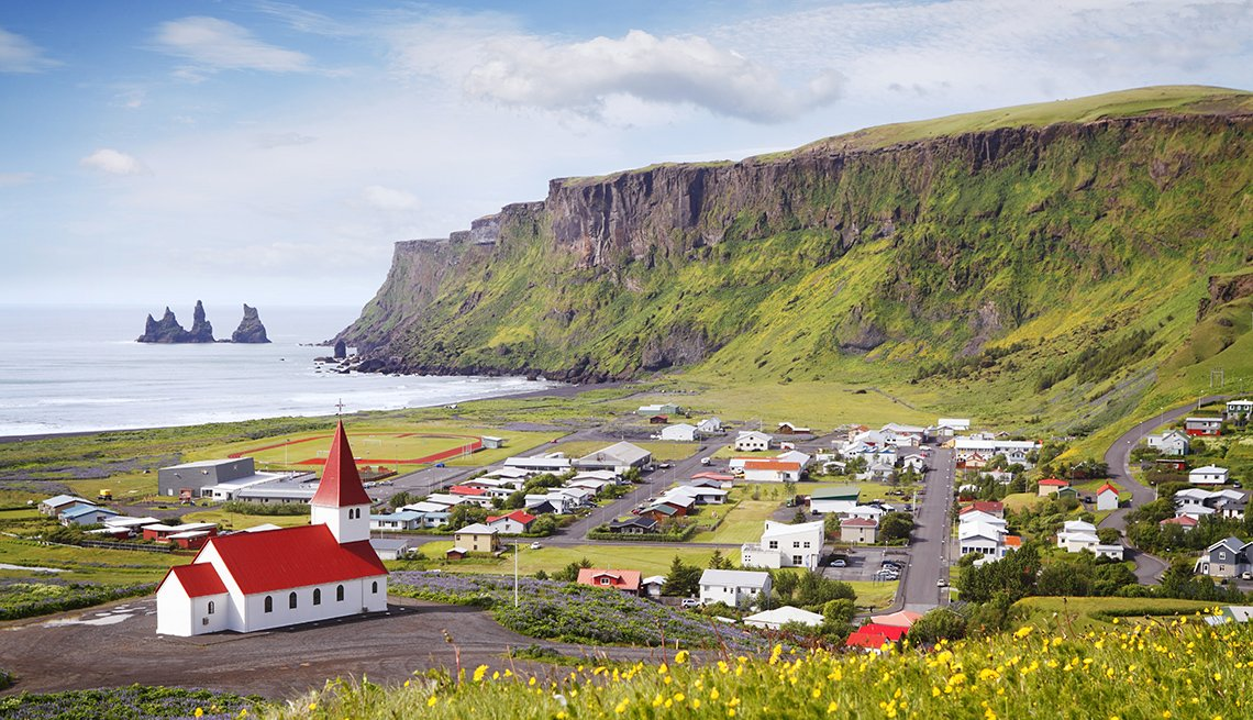 A church with red roof and surrounding village in Iceland.