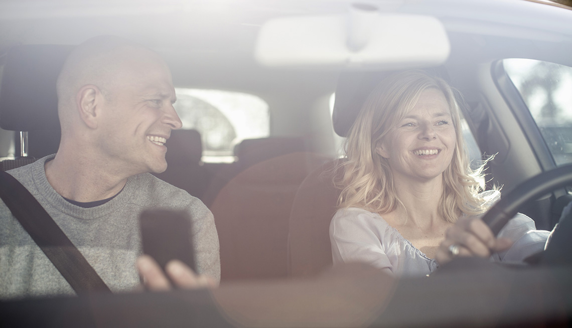 man and woman in car driving, using GPS