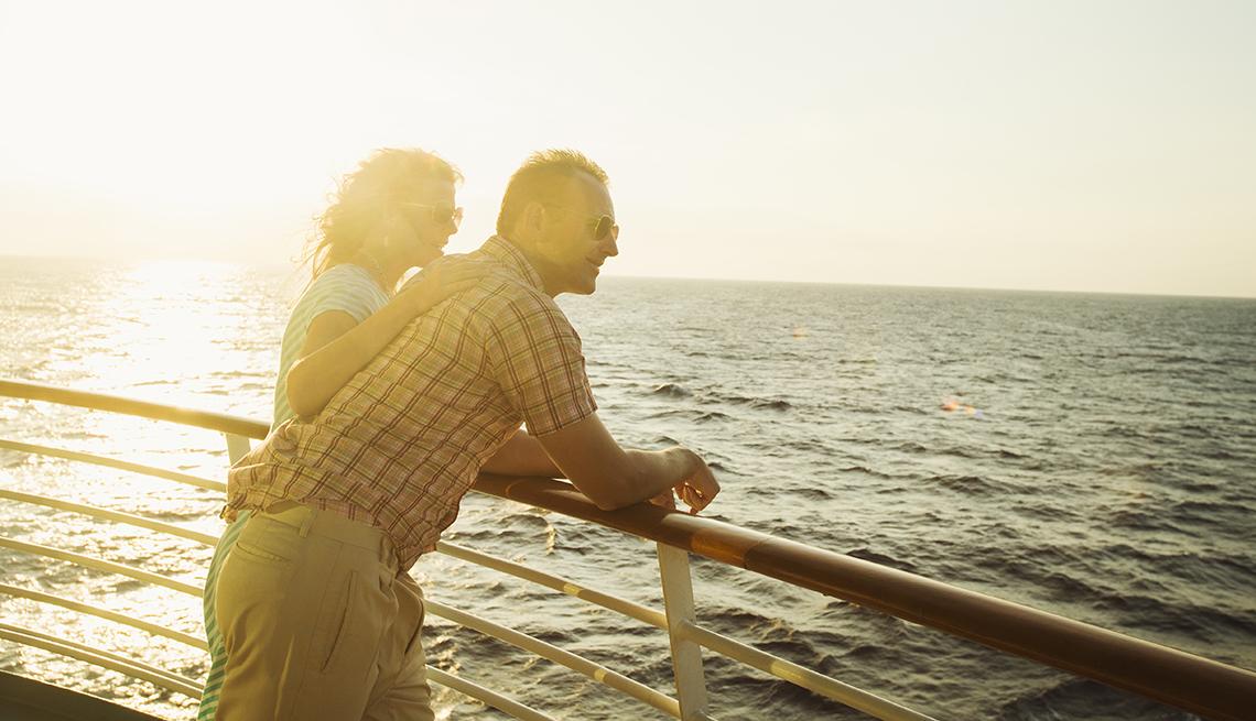 Pareja mayor ve hacia el horizonte desde la cubierta de un barco.