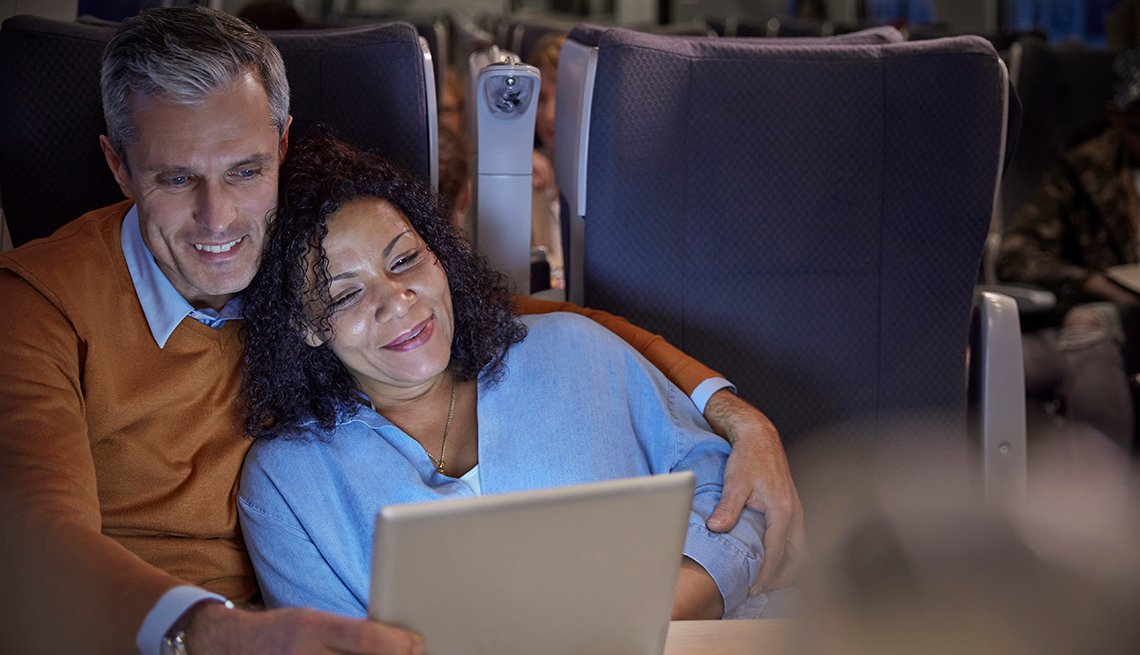 couple watching movie on tablet while on a train