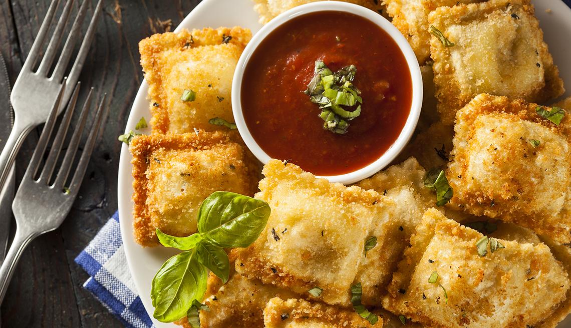 Ravioles fritos caseros con salsa marinara y albahaca.