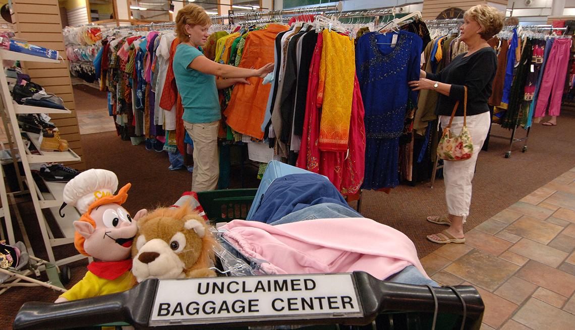 Dos mujeres en el centro de equipaje no reclamado de un aeropuerto.