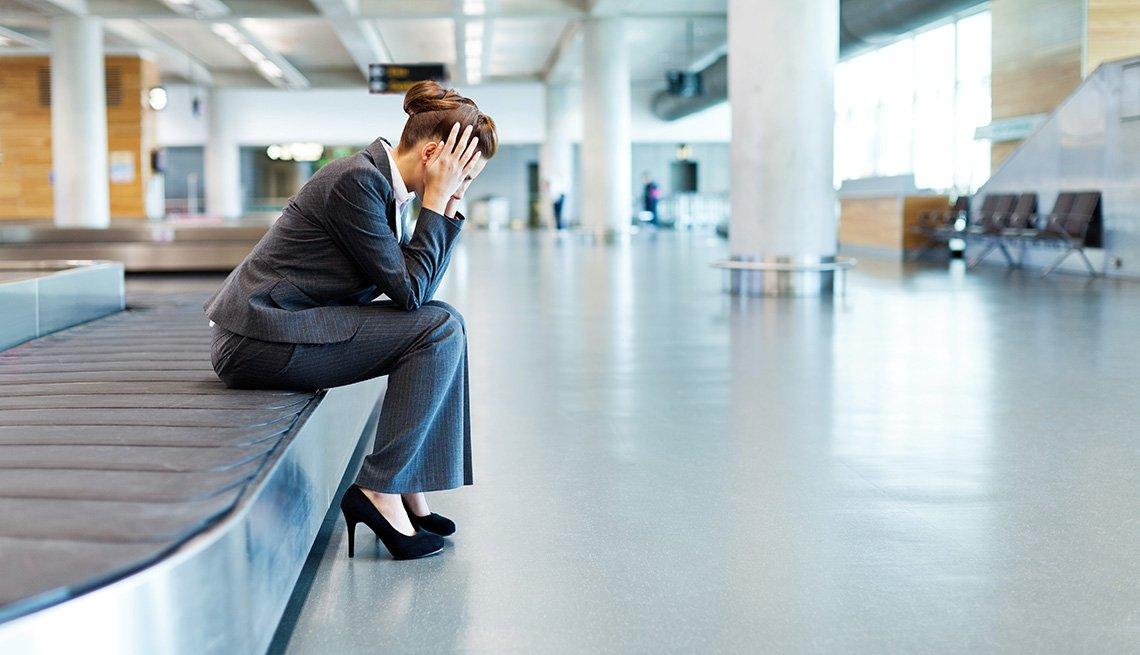Mujer está sentada en una banda transportadora de equipaje de un aeropuerto.