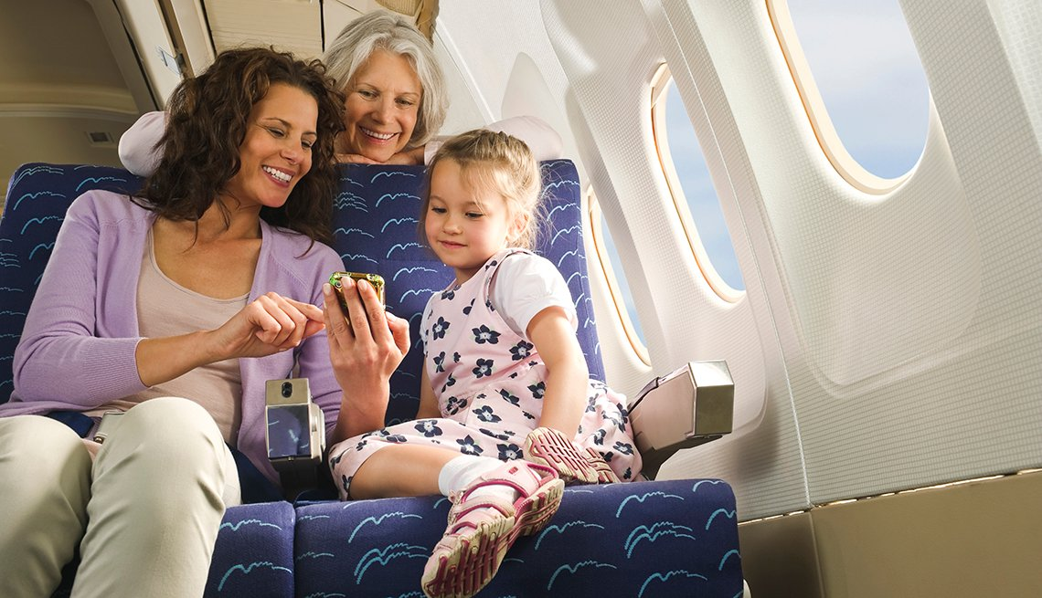 Family looking at cell phone aboard airplane
