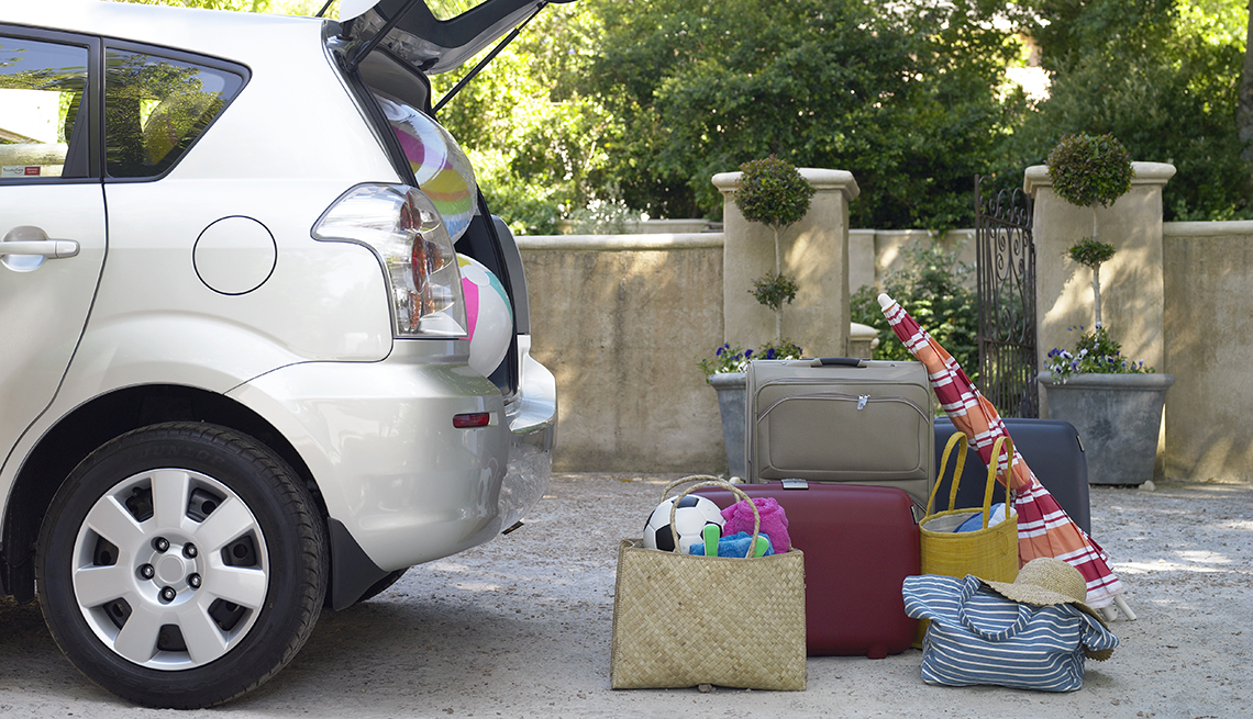 Car with trunk door open and beach items and luggage