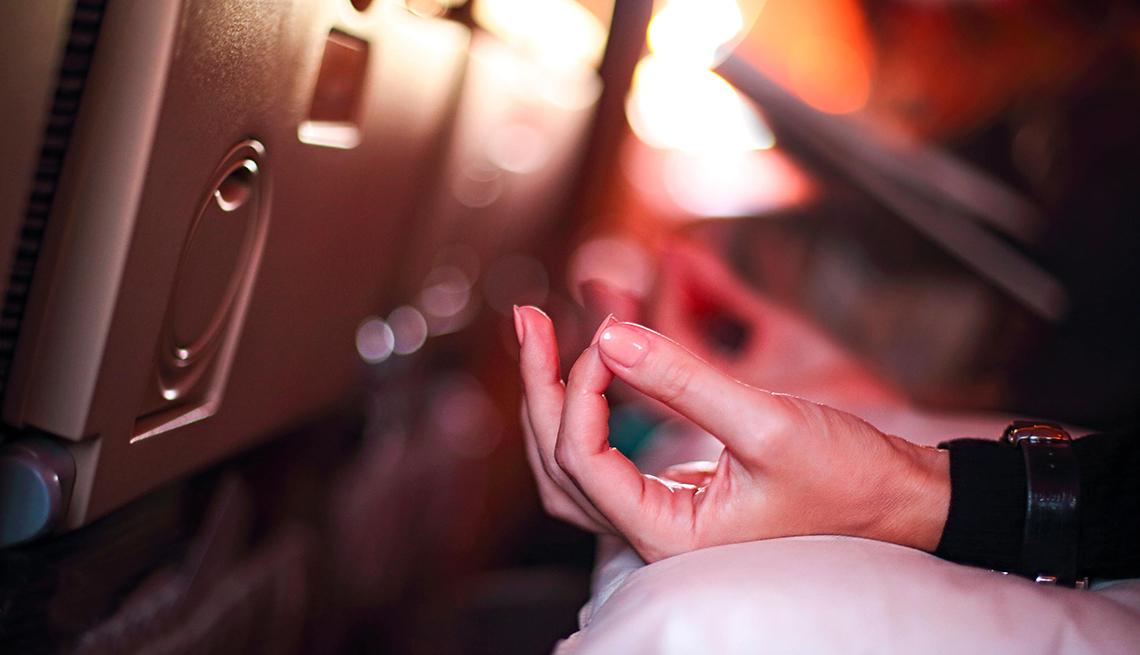 Persona en avión con aerofobia asustada de volar con miedo mientras está sentada en el asiento del avión y haciendo yoga para relajarse.