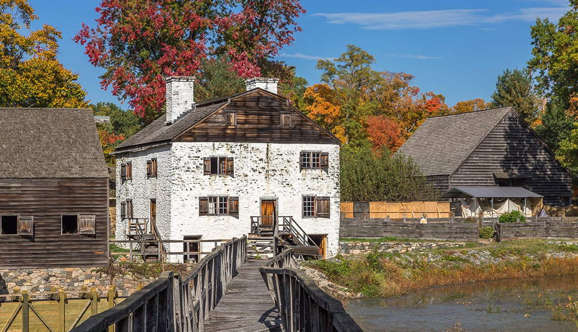 Puente a Philipsburg Manor, casas, cielo azul y árboles de color otoñal en Sleepy Hollow, Hudson Valley, Nueva York.