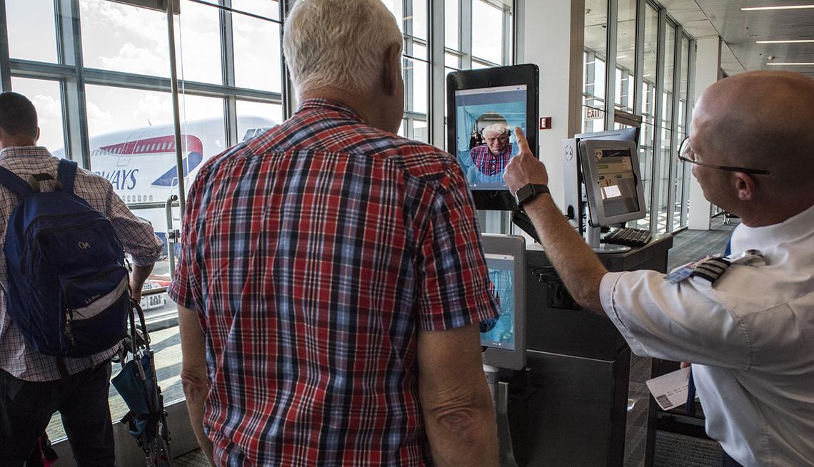 Hombre parado frente a un escáner biométrico de reconocimiento facial en un aeropuerto.