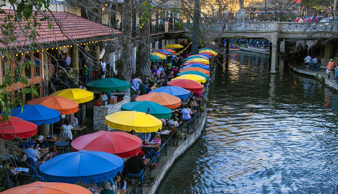 Área urbana con una red de pasarelas y restaurantes a lo largo de las orillas de un río.