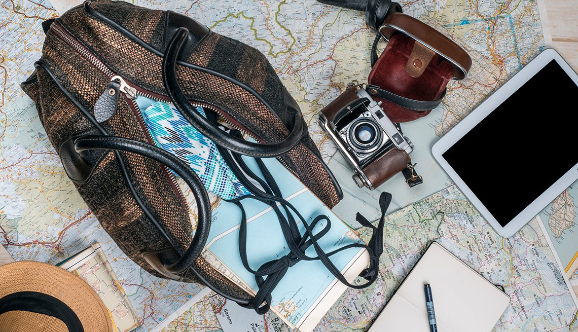 open suitcase on a map with camera and tablet