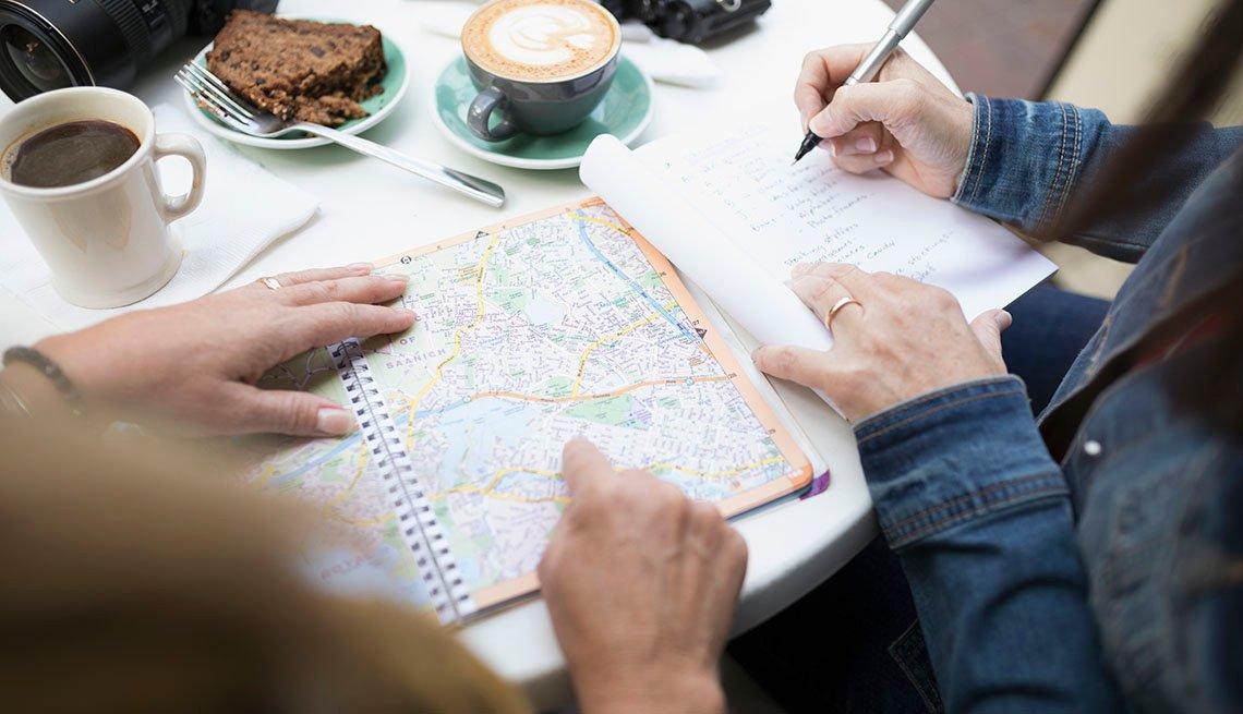 Amigos revisan un mapa mientras toman café.