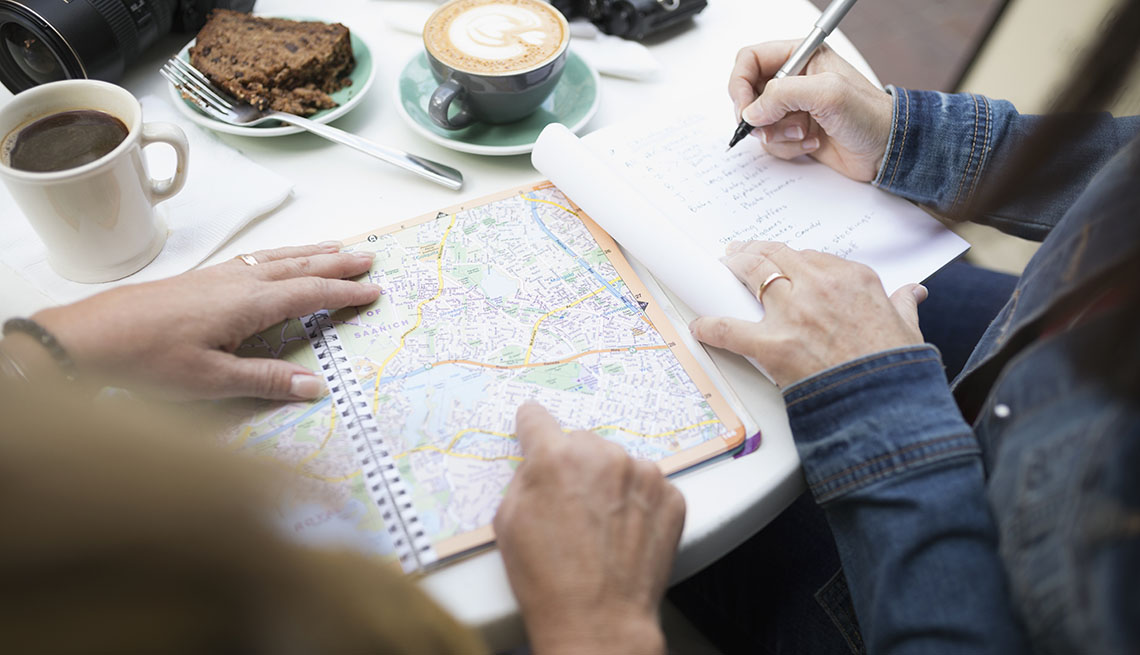 Friends at a cafe reviewing a map while drinking coffee
