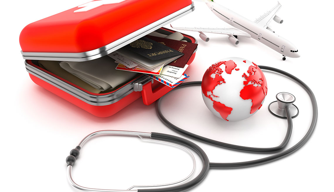 First-aid kit designed as a suitcase with passports, plane tickets and clothes inside, stethoscope and globe isolated on white