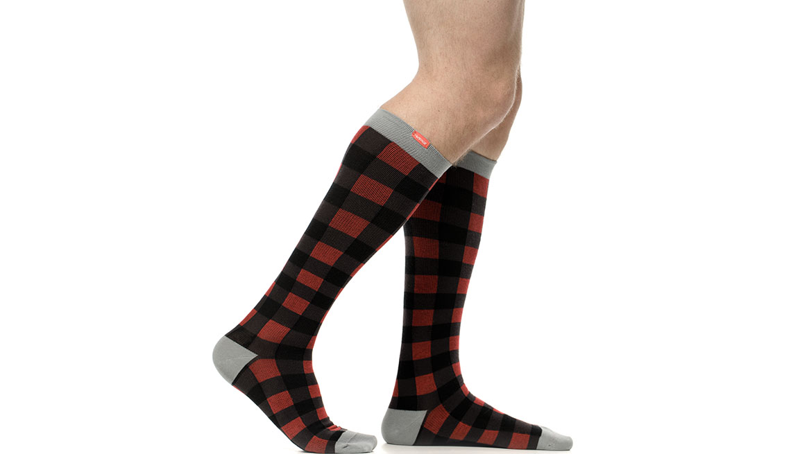 An image of a man wearing plaid knee high compression socks