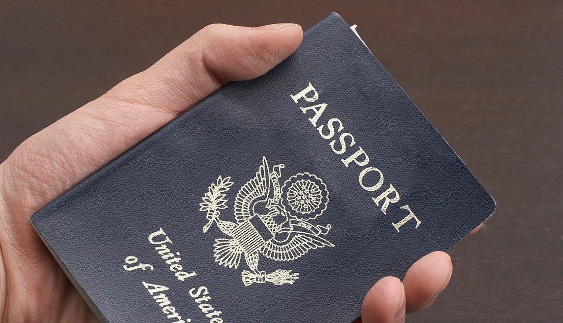 Persona sostiene un pasaporte en la mano