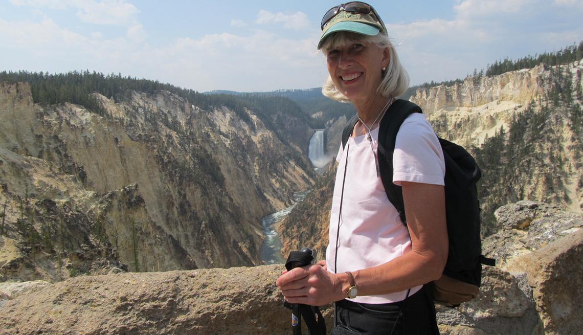 Mujer sonríe mientras pasea por un parque nacional