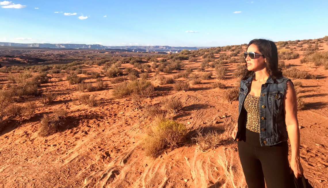 Carmen Dominicci parada en medio de un terreno desértico