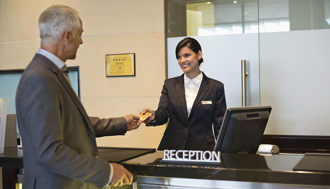 man paying bill at hotel front desk