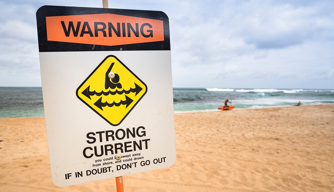 Sign on the beach that reads: Warning: Strong Current. If in doubt, don't go out