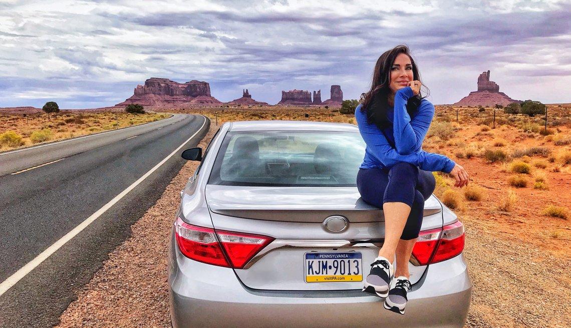 Carmen Dominicci sentada en el exterior de la parte trasera de un automóvil