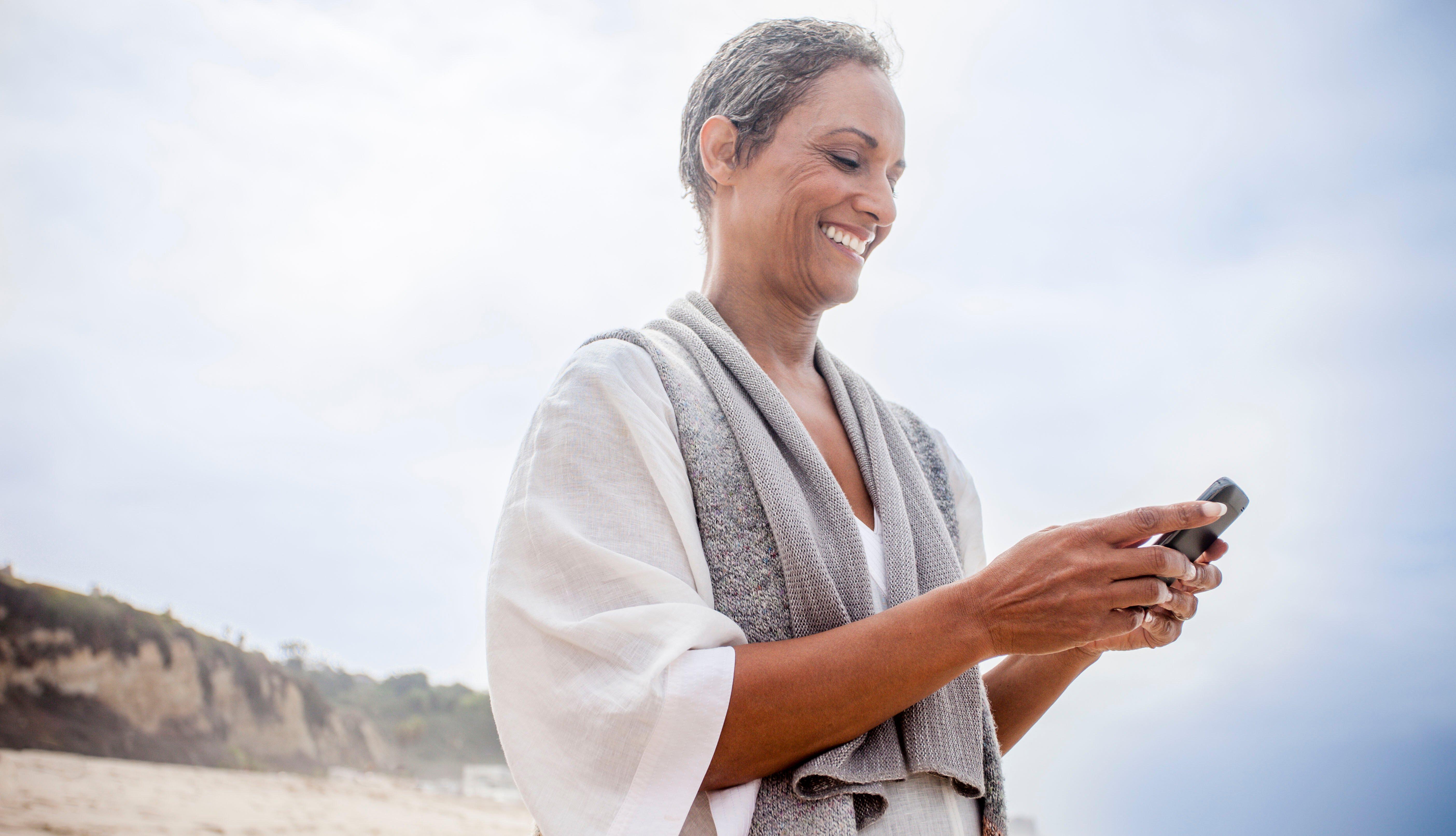 Mujer sostiene un teléfono inteligente en la playa