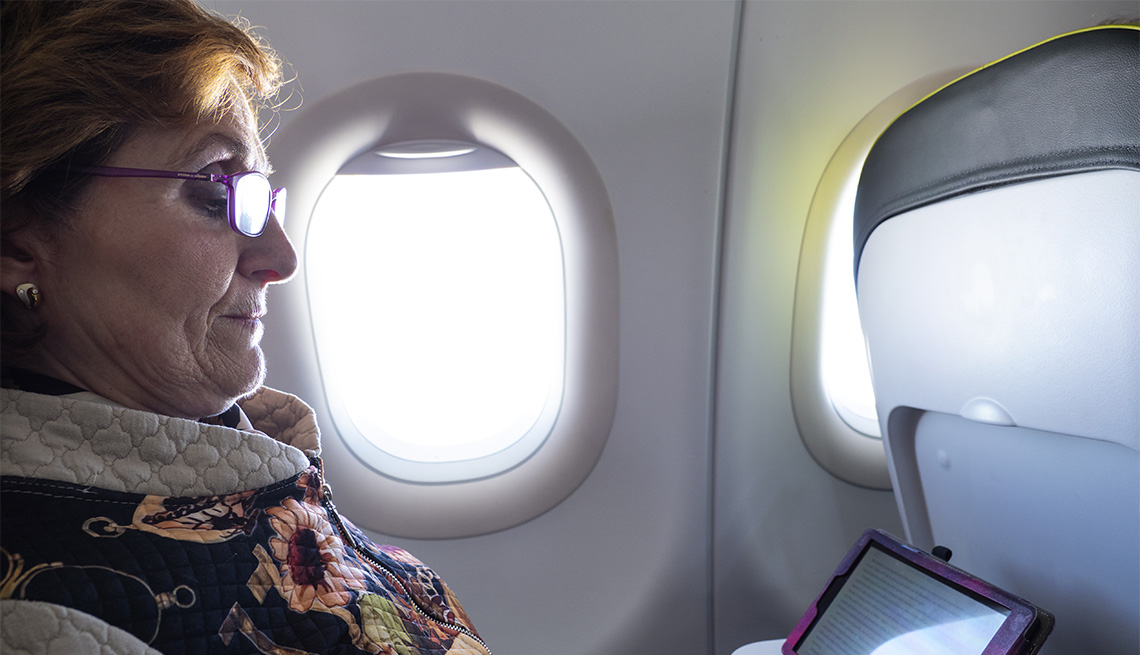 Female airline passenger sitting in a window seat, looking at tablet