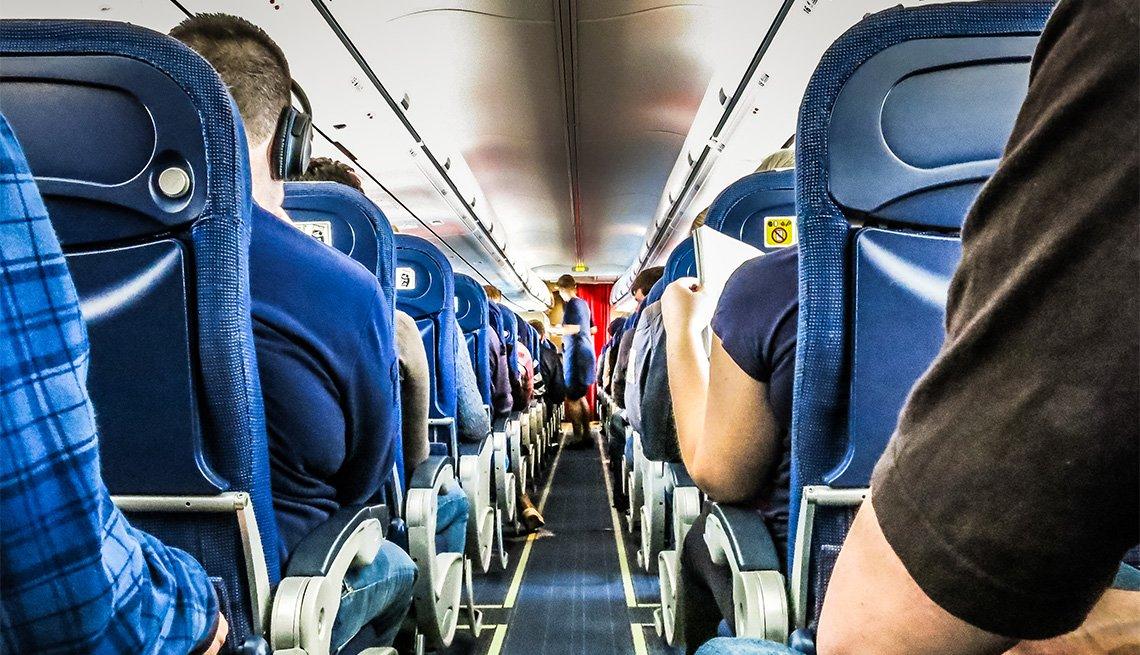 Pasajeros de un avión sentados en sus sillas
