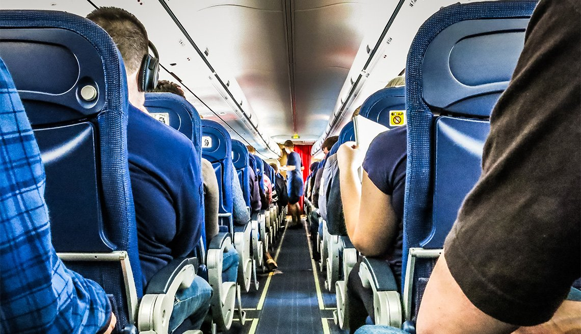 people sitting in seats inside an airplane