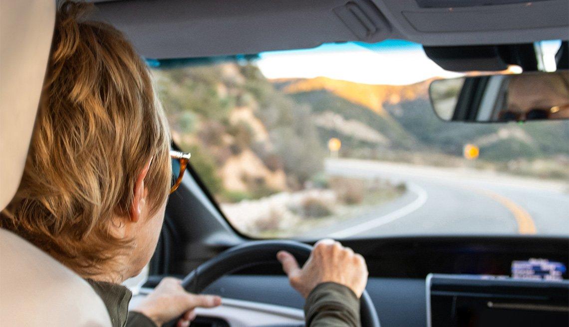 Mujer conduce su auto en las montañas en un día soleado