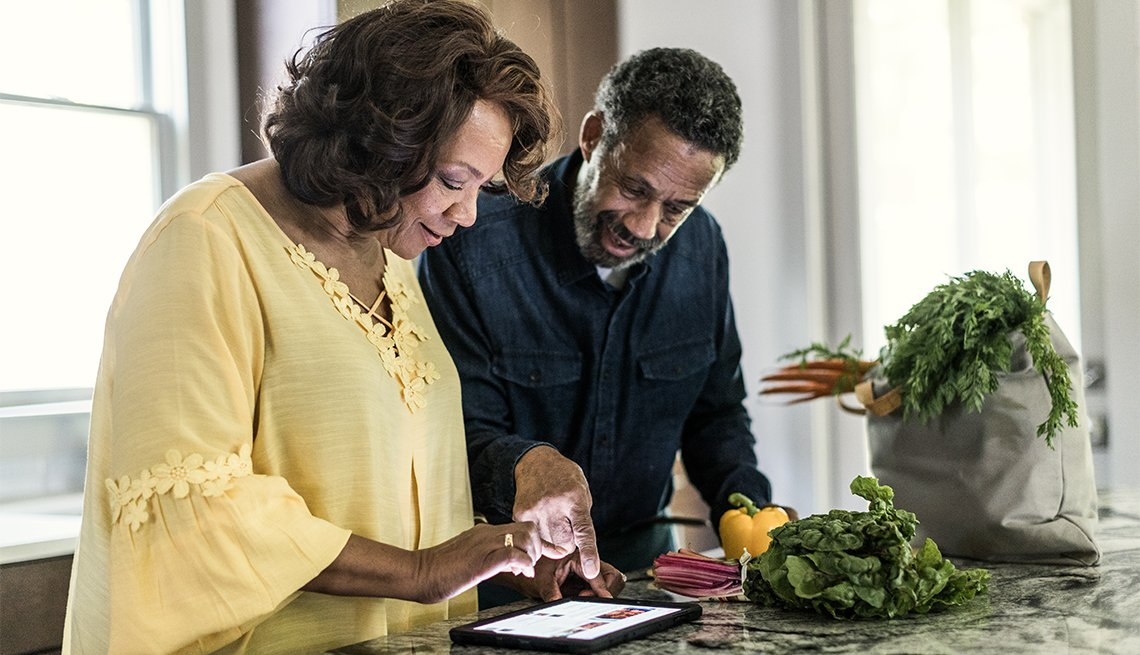 couple using tablet in kitchen to cook a meal