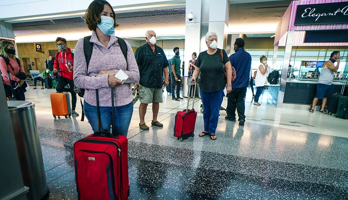 several people wearing masks and standing well apart from one another in an airport gate area with their travel bags