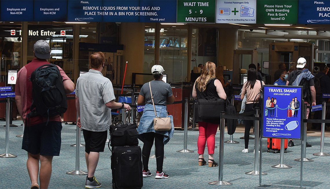 A sign reminding passengers to stay 6 feet apart is seen at a screening checkpoint at Orlando International Airport