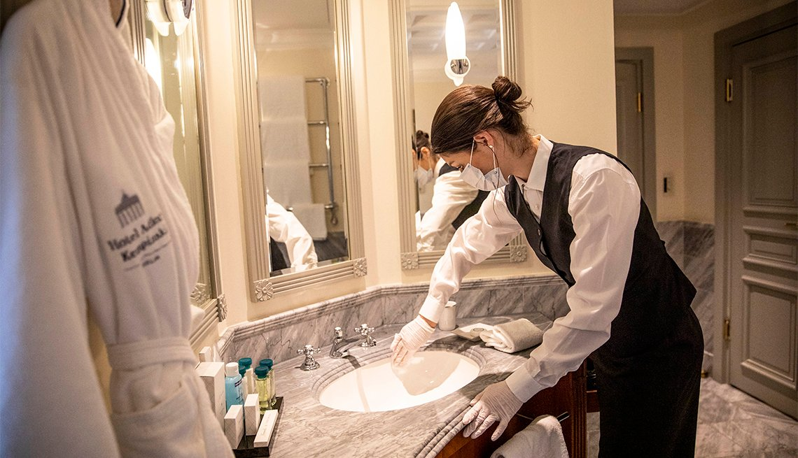 A housekeeper cleans the bathroom for the benefit of media present in The Presidential Suite at the Hotel
