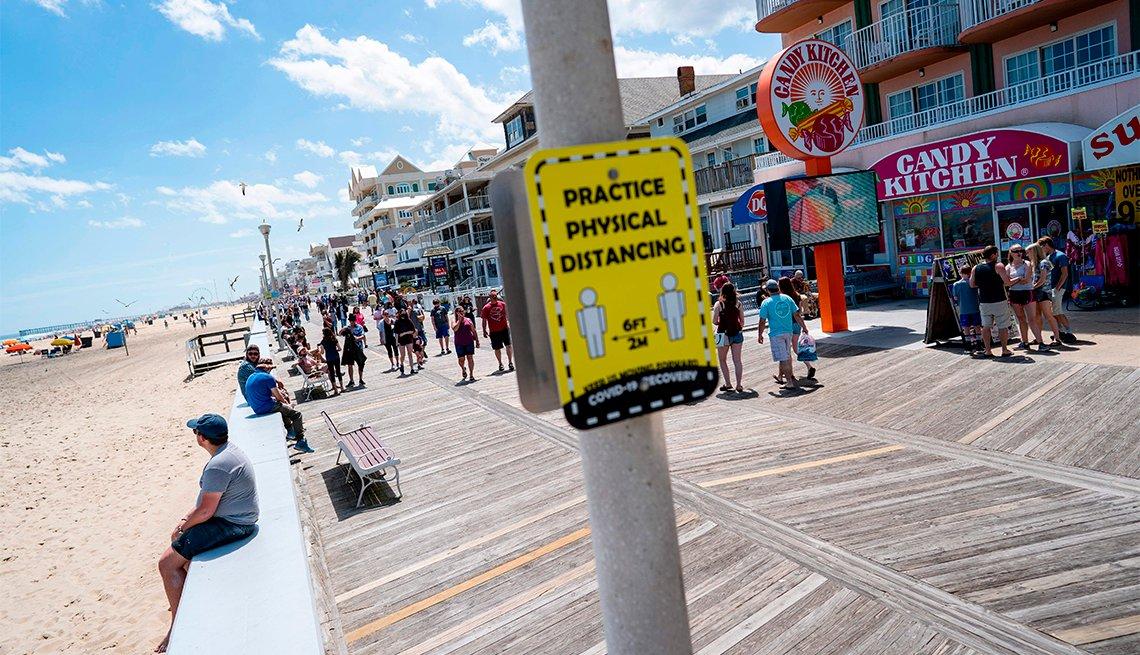 Gente pasa junto a un letrero que aconseja el distanciamiento social en un paseo marítimo