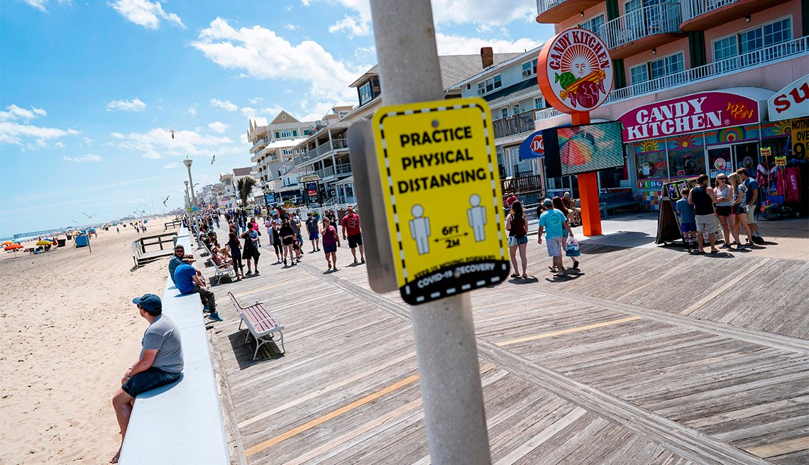 People walk past a sign advising about social distancing on the boardwalk during the Memorial Day holiday weekend amid the coronavirus pandemic on May 23, 2020 in Ocean City, Maryland
