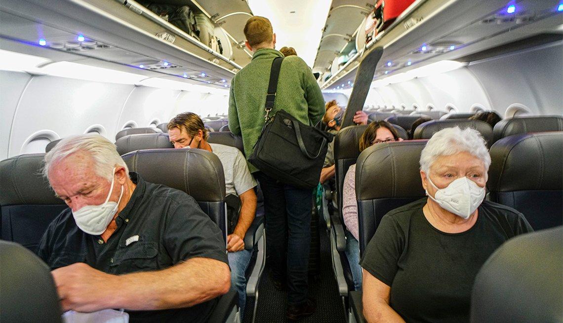 Pasajeros con mascarillas abordan un avión