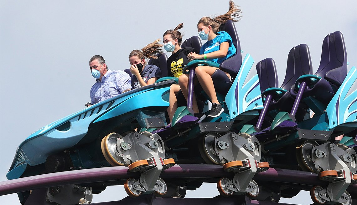 Sea World Orlando guests don masks to ride the Mako roller coaster, in Orlando, Fla.