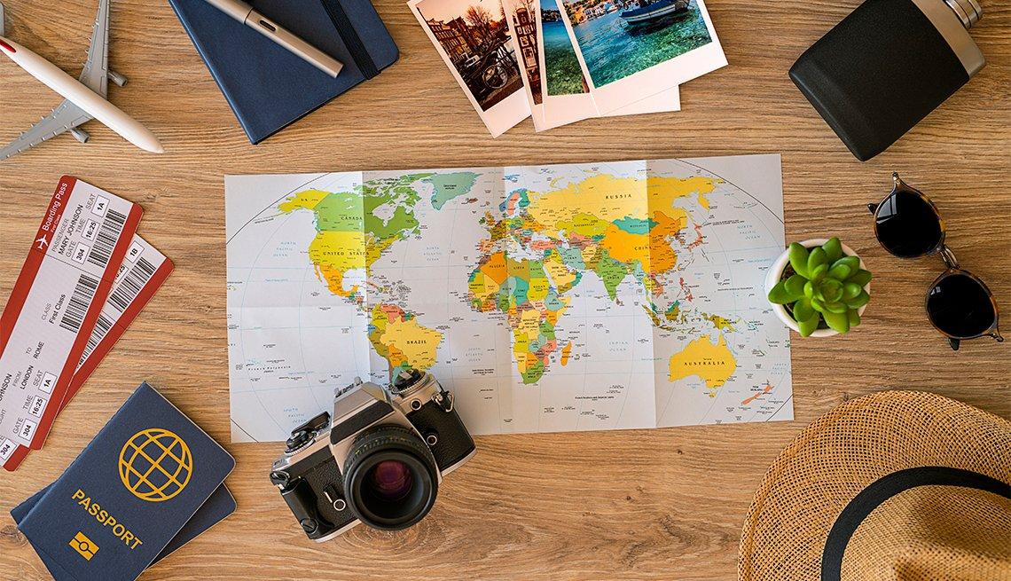 Cosas de viaje en un escritorio: mapa, lentes de sol, cámara, boletos y pasaporte