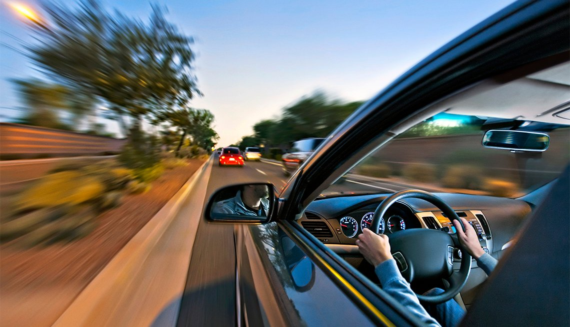 Hombre conduce su auto en la carretera