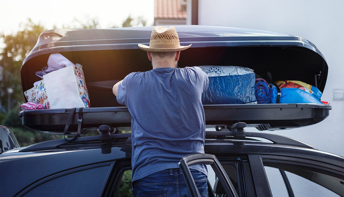 man packing car before roadtrip