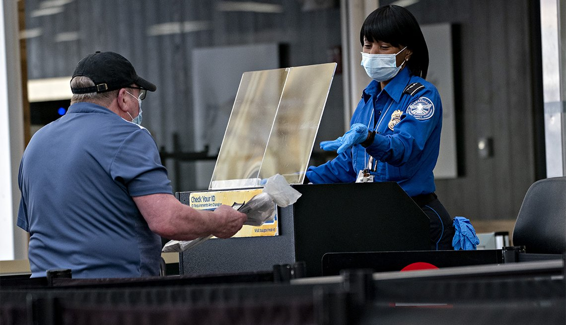 Una agente de la TSA con mascarilla y detrás de una barrera protectora, revisa los documentos de un viajero