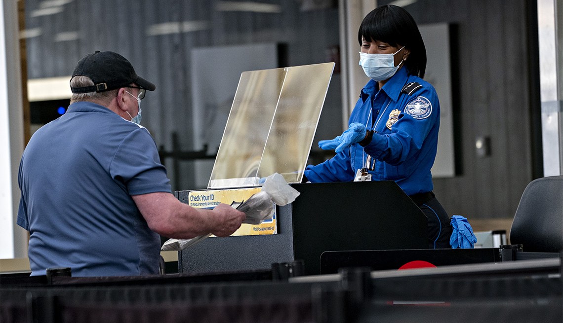 A Transportation Security Administration (TSA) agent wears a protective mask and stands behind a protective barrier while screening a traveler.