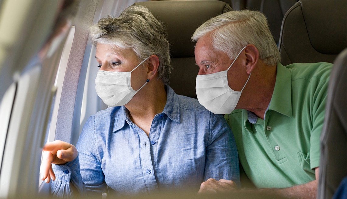 Couple traveling by plane wearing facemasks and looking through the window - travel during the COVID-19 pandemic