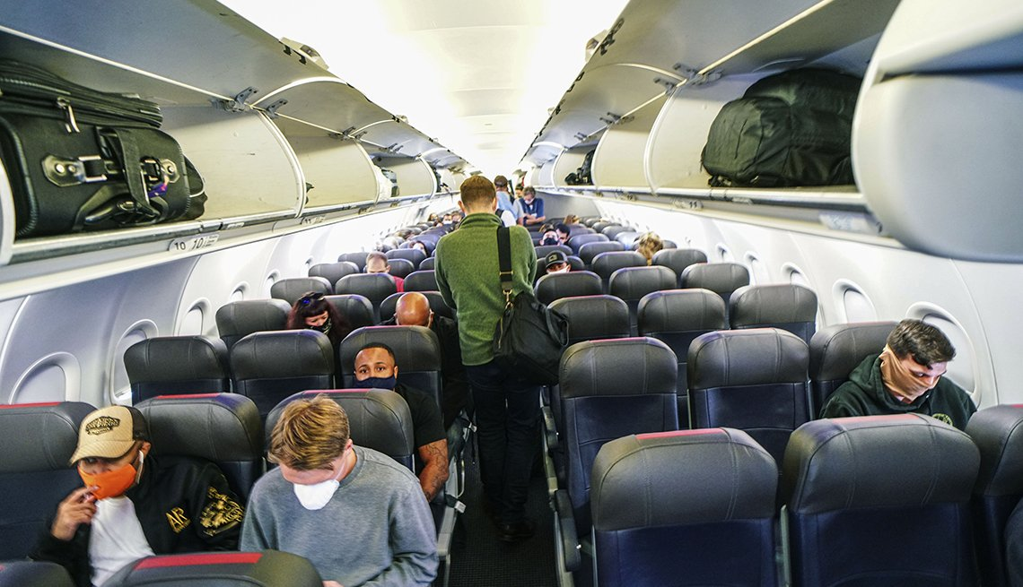 looking down the center aisle of a mostly empty airplane being boarded during the coronavirus pandemic