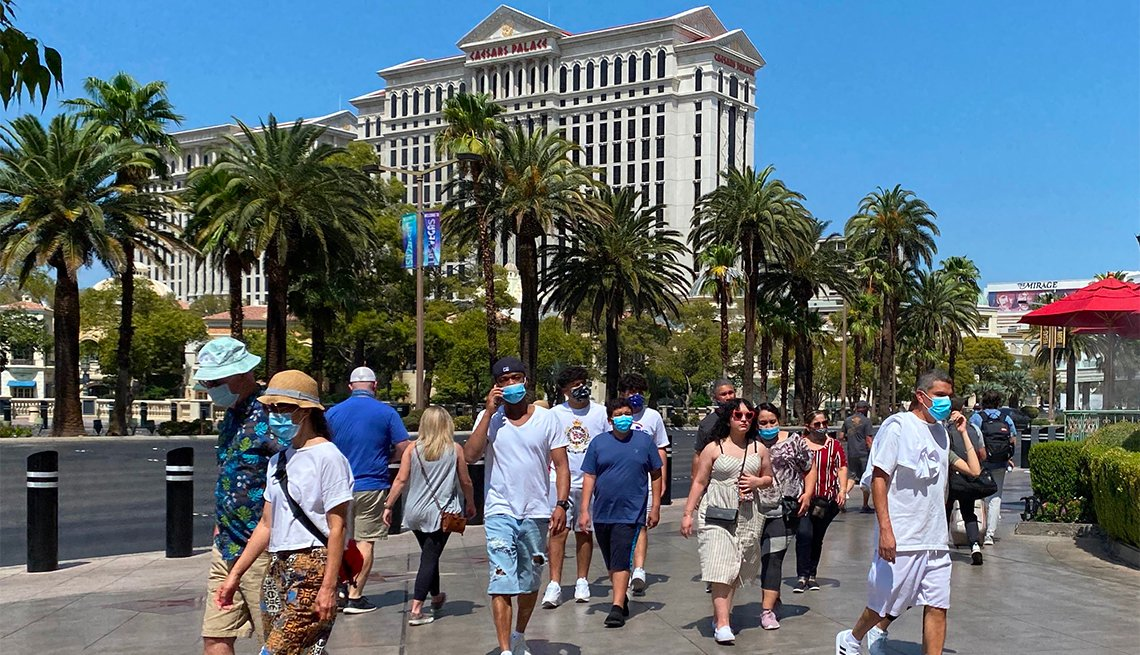 Tourists are wearing masks as they walk on the Strip in Las Vegas