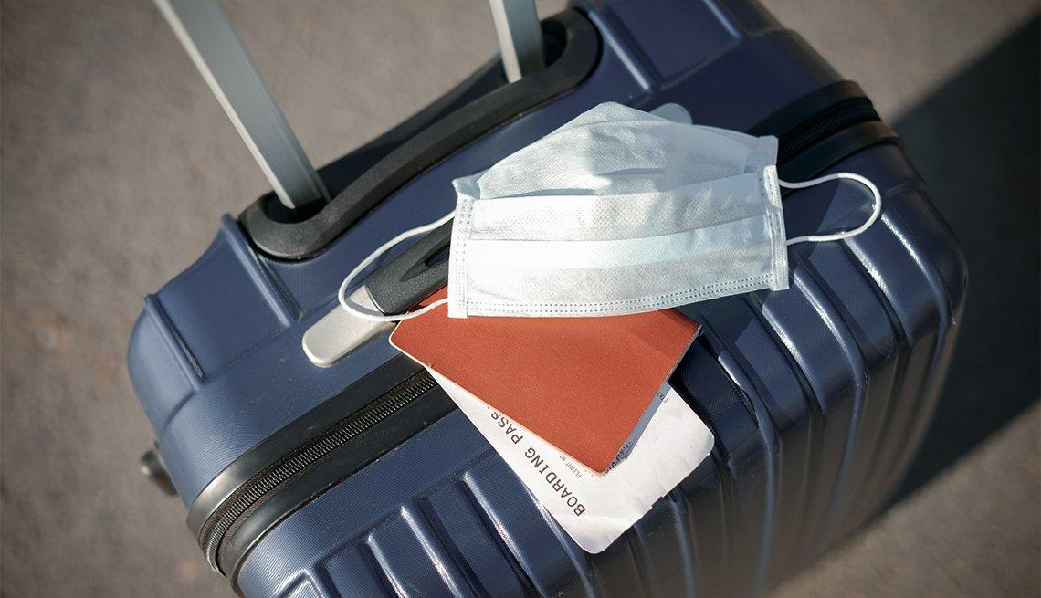 Maleta de viaje, pasaporte, pasabordo y máscara